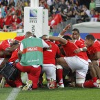 Tongan players embrace in prayer after beating France in Wellington.