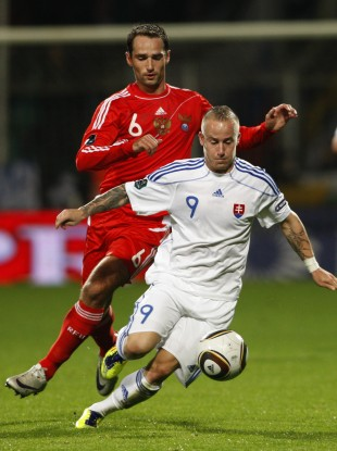 Roman Sirokov, left, from Russia challenges for the ball with Miroslav Stoch.