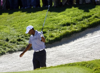Woods looks unimpressed after escaping a bunker on the 13th hole of his second round.