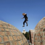 A boy jumps between roof domes as he plays during the annual Tbilisoba City Day celebration in Tbilisi, Georgia, Saturday, Oct. 8, 2011, with Metekhi Church, built in 13th century, seen in the background. 
