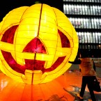 A young woman walks closer to feel a big pumpkin lantern built up on a street for the Halloween and Hallowmas in Shenyang city, northeast Liaoning province, 24 October 2011. (PA)