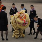 Flight attendants of All Nippon Airways Boeing 787 laugh during a lion dance at Hong Kong International Airport for the airplane's inaugural commercial flight from Japan. 