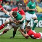 Ireland's Brian O'Driscoll tackled by Dan Lydiate and Rhys Priestland of Wales.