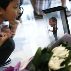 A boy looks at the figure of Steve Jobs where flowers laid in tribute to Steve Jobs at an Apple retail store in Hong Kong.  (AP Photo/Kin Cheung)