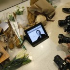 Fans and media take picture of a iPad announcing the death of Steve Jobs at an Apple store in Honk Kong.  (AP Photo/Kin Cheung)