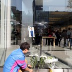 A young Chinese man leaves flowers for Steve Jobs outside an Apple store in Sanlitun, Beijing, China. (Zhang jusheng/AP/Press Association Images)