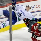Vancouver Canucks' Dale Weise, left, is upended in a collision with Minnesota Wild's Cal Clutterbuck.