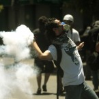 A masked student sends back a tear gas canister lanced by riot police during clashes in Valparaiso, Chile on Wednesday. 