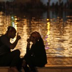A newly married couple sit by the water tank of the illuminated Bangla Sahib Sikh temple on the birth anniversary of Guru Nanak in New Delhi, India. 