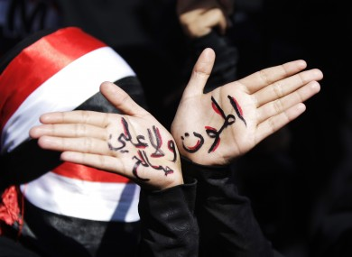 A Yemeni female protestor displays her hands with Arabic writing that reads,