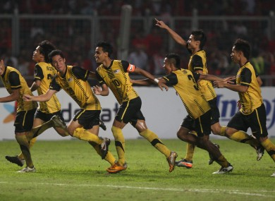 Malaysian players celebrate upon winning their SEA Games soccer final match against Indonesia, at Gelora Bung Karno in Jakarta, Indonesia, Monday, Nov. 21, 2011.