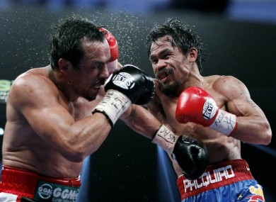 Manny Pacquiao (right) hits Juan Manuel Marquez
