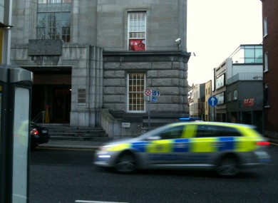 A squad car passing by the building on Kildare Street just after 3.30pm today. The USI banner is visible in the window.