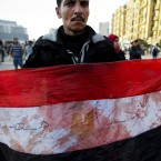 An anti-government protester displays an Egyptian flag, covered with blood, during clashes in Tahrir in Cairo on 2 February. (AP Photo/Tara Todras-Whitehill/PA Images)