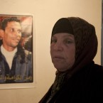 Manoubiyeh Bouazizi, the mother of Mohamed Bouazizi, the local fruit vendor who set himself on fire in December 2010, stands next to his picture at the family home in the town of Sidi Bouzid, Tunisia, on 8 March, 2011. (AP Photo/Giorgos Moutafis/PA Images)