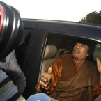 Muammar Gaddafi sits in a car in Tripoli, Libya, in April 2011. After months in hiding, Gaddafi was found and killed by rebel fighters in October. (AP Photo/Pier Paolo Cito/PA Images)