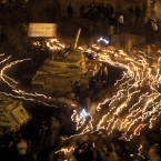 Anti-government protestors hold candles as they walk around an Egyptian Army tank at Tahrir Square, Cairo just days before Mubarak's resignation in February. (AP Photo/Emilio Morenatti/PA Images)