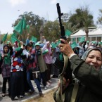 In this photo taken on a government-organised media tour, a Libyan woman fires in the air during a graduation ceremony after a weapons training course in Tripoli, Libya, on 26 June. Government spokesman Moussa Ibrahim said Libyan officials gave out 1.2 million weapons and were training people all around territories under Gaddafi's control as