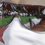 Syrian anti-Assad protesters are reflected on a masked protester's sunglasses during a protest in front of the Arab League headquarters in Cairo on 12 November, 2011. (AP Photo/Amr Nabil/PA Images)