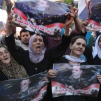 Pro-Syrian regime protesters, hold up portraits of Syrian President Bashar Assad with Arabic words: