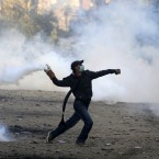 A demonstrator protesting against Egypt's military rule throws a tear gas cannister during clashes with riot police near Tahrir Square in Cairo on 21 November, 2011. (AP Photo/Khalil Hamra/PA Images)