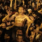 A protester with writing Arabic on his chest that reads,