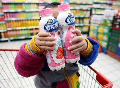 A child holds two bottles of strawberry-flavoured Pulpy Milky at a Shanghai supermarket