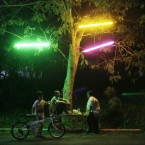 An Indonesian family chat while enjoying evening snacks under colored fluorescent tubes hanging on a tree in Yogyakarta, central Java (AP Photo/Dita Alangkara)