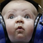 Three-month old Henry Hirschey wears headphones while attending an NCAA college basketball game (AP Photo/Gerry Broome)