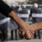 Anti-government protesters link hands to form a barrier between fellow protesters and riot police on 17 December in Abu Saiba village. Shortly after, police used tear gas and sound bombs to disperse thousands who had gathered in the third straight day of clashes. (AP Photo/Hasan Jamali/PA Images)