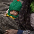 An Indian homeless mother tries to keep her baby warm by a road side on a cold in Allahabad, India. (AP Photo/Rajesh Kumar Singh)