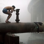 An Indian man drinks from a tap on a water pipe as he bathes outside near a sewage drain on a cold and foggy morning in New Delhi, India, Tuesday, Dec. 20, 2011. Though India is famous for its brutally hot summers, temperatures fall sharply for a few weeks in December and January. Poor people, particularly those living on the streets, are the worst hit. (AP Photo/Kevin Frayer)