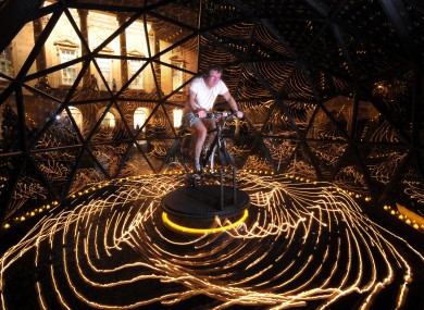Lighting artist Bruce Munro rides the bike powering his Star Turn installation at a museum in Bath