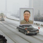 The funeral motorcade including a car exhibiting a large portrait of the late Kim Jong Il drives through Pyongyang on a snowy road on Dec. 28, 2011. (Kyodo)