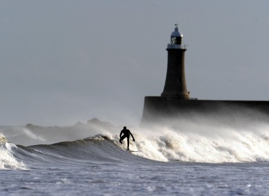 A surfer makes use of the strong North Sea waves at Longsands Beach in Tyne and Wear, north-east England earlier today.