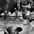 Muhammad Ali crouches on the canvas as Joe Frazier circles in the background after Ali slipped during the 11th round of their title fight at Madison Square Garden in New York on 1971.