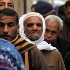 Egyptian voters line up outside a polling centre in Assuit, Egypt as voting opens in the first post-Mubarak elections. Clashes continue between protesters and the military over the army concil's continuing rule: at least 42 people have died in the latest clashes. (AP Photo/Khalil Hamra/PA Images)