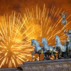 Fireworks light the sky at the Brandenburg Gate in Berlin shortly after midnight, greeting the New Year (AP Photo/Michael Sohn).