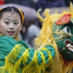 A young dancer from the Fairfax Chinese dance troupe from the Washington DC area performs in heavy rain during the annual London New Year's Day parade (AP Photo/Alastair Grant).