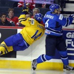 Team Sweden's Max Friberg collides with the advertising board during the second period of a world junior hockey championships semi-final game last Tuesday. 