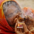 A Hindu women smokes marijuana as she sits at the confluence of rivers Ganges, Yamuna and mythical Saraswati, on