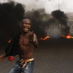 An angry youth protests in front of a burning barrier following the removal of a fuel subsidy by the government in Lagos, Nigeria. (AP Photo/Sunday Alamba)