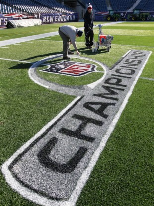 New England Patriots ground crew workers apply paint to an NFL football championship playoff logo at Gillette Stadium.