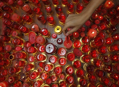 A Filipino-Chinese lights candles while praying inside a Chinese temple in celebration of the Chinese New Year at Manila's Chinatown district Monday Jan. 23, 2012 in the Philippines.