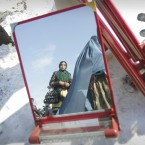 An Afghan woman is reflected in a mirror displayed for sale in Kabul, Afghanistan, Monday, Jan. 23, 2012. (AP Photo/Ahmad Nazar)