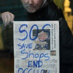 Frank McQuade puts up posters calling for the Occupy Dame Street camp to be dismantled. Photograph: Niall Carson/PA Wire
