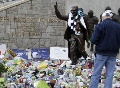 A statue of legendary Penn State football coach Joe Paterno is surrounded by flowers and items left by fans today.