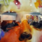 Visitors are reflected in the glass of a painting at the opening night of the India Art Fair in New Delhi, India. Wednesday, Jan. 25, 2012. (AP Photo/Tsering Topgyal)