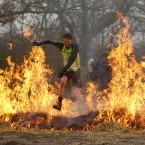 A competitor runs through flames at the annual Tough Guy event. (AP Photo/Jon Super/PA Images)