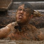 Emerging from a very muddy water obstacle. (AP Photo/Jon Super/PA Images)
